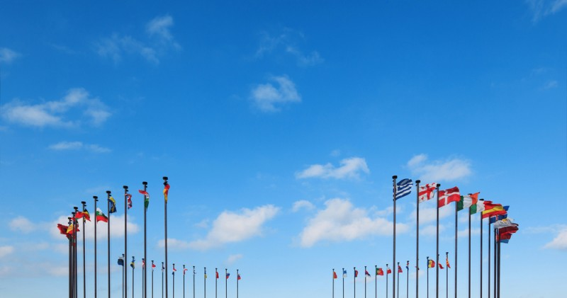 Flags of different countries on a flagpole against a blue sky
